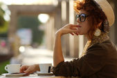Hiipster girl sitting in a cafe — Stock Photo