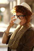 Hipster girl drinking coffee outdoors — Stock Photo