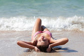 Beautiful young girl sunbathing in tidal waves — Stock Photo