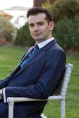 Junger mann im anzug sitzen im freien — Stockfoto