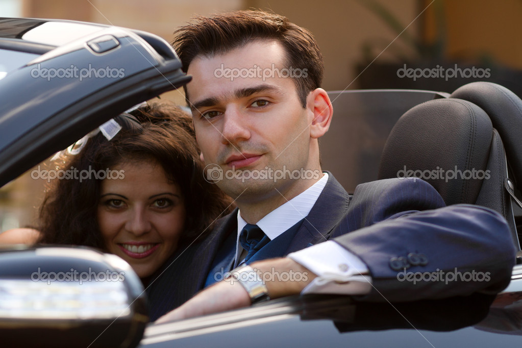 Beautiful young couple sitting in cabrio car outdoors — Stock Photo #13992127