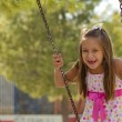 Stock Photo: Little girl swinging in the park