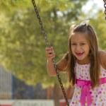 Little girl swinging in the park — Stock Photo #14185700