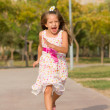 Funny little girl running in the park — Stock Photo