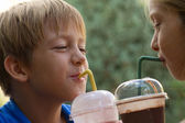 Funny little children drink milkshake — Stock Photo