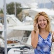 Stock Photo: Blond girl with phone on pier