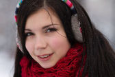 Girl in earplugs outdoors in winter — Stockfoto