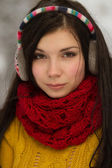 Girl in earplugs outdoors in winter — Photo