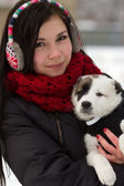 Girl with a puppy outdoors in winter — Stock Photo