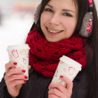 Cute girl in earplugs with coffee cup - Stockfoto