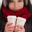 Stock Photo: Cute girl in earplugs with coffee cup