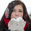 Stock Photo: Girl blowing fluffy snowflakes