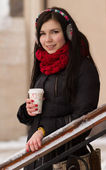 Cute girl in earplugs with coffee cup — Stockfoto