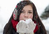 девушка дует пушистые снежинки — Стоковое фото