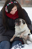 Teen girl with pug puppy in snow — Stock Photo