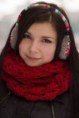 Girl wearing earplugs outdoors in winter — Photo