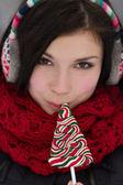 Dziewczyna w zatyczki do uszu, lizanie lizaka — Zdjęcie stockowe