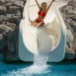 Blond girl riding slide in waterpark - Stock Photo