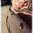 Bride shows wedding bouquet from window of car — Stock Photo