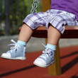 Stock Photo: Feet of unrecognizable baby swinging on playground