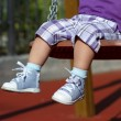 Feet of unrecognizable baby swinging on playground — Stock Photo