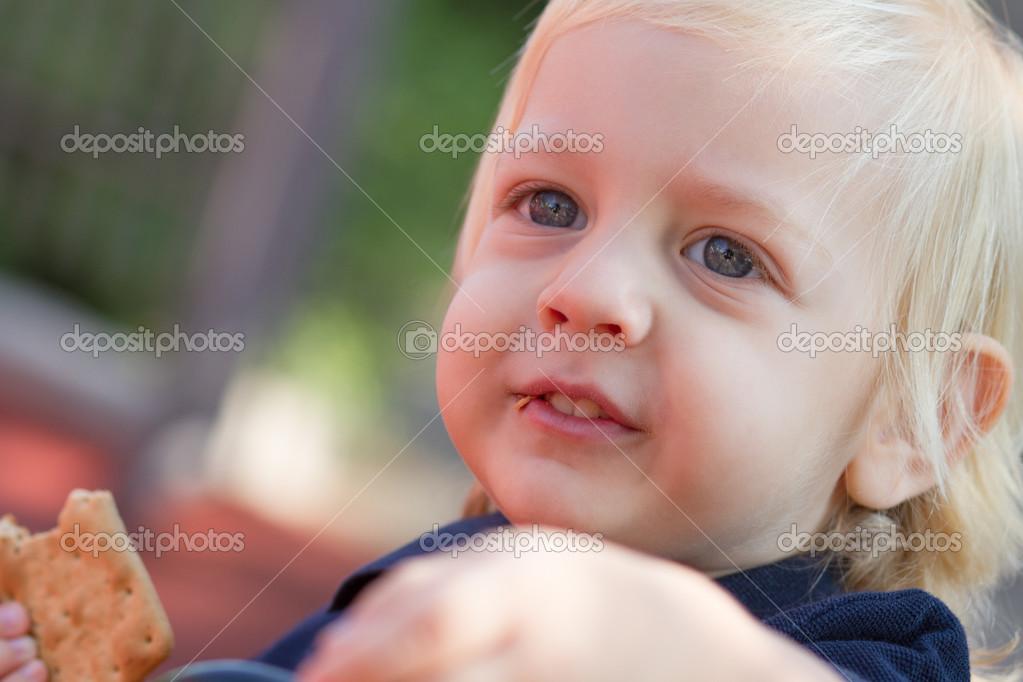 最可爱的白肤金发婴儿男孩在操场上吃美味饼干的肖像 — 照片作者