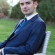 Young man in suit sitting outdoors - Stock Photo