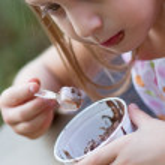 Funny little girl eats ice-cream — Stock Photo