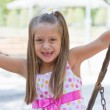 Funny toothless little girl on a playground — Stock Photo #24559309