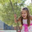 Little girl swinging in the park — Stock Photo
