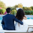 Young wife and husband sitting at the pool — Stock Photo #24559591