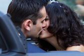 Happy newlyweds kissing in cabrio — Stock Photo