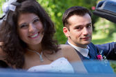 Happy newlyweds in a cabrio — Stock Photo