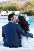 Giovane moglie e marito, baci in piscina — Foto Stock