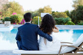 Young wife and husband sitting at the pool — ストック写真