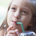 Funny little girl drinks milkshake — Stock Photo #24562275
