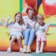 Stock Photo: Mother and her daughters sitting on bouncing castle