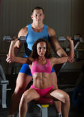 Instructor assisting girl with dumbells — Stock Photo