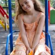 Llittle girl swinging on the playground — Stock Photo