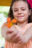 Cute little girl giving you the flower — Stock Photo
