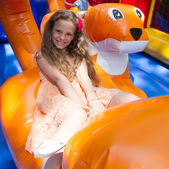 Cute little girl plays in bouncing castle — Stock Photo
