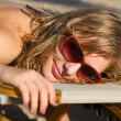 Blond girl sunbathing on a lounge — Stockfoto