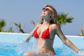 Blond girl enjoying the water in pool — Stock Photo