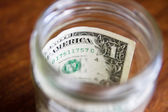 Stash of savings - one dollar in a jar — Stock Photo