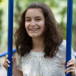 Happy teenage girl swinging in the park — Stock fotografie