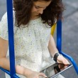 Teenage girl with tablet pc on a swing — Stock Photo #28476117