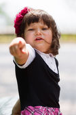 Sad little girl pointing with finger — Stock Photo