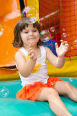 Little girl playing with bubbles — Stock Photo
