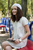 Teenage girl with trendy tablet pc in park — Stock Photo