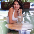 Attractive brunette girl in a cafe outdoors — Stock Photo